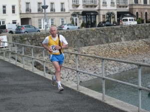Dave Parsons completing the Guernsey Half Marathon with Ian Graham 'hiding' behind the sea wall a short distance behind