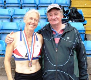 Janet Dickinson displays her Heptathlon Gold Medal with coach Paul Rees