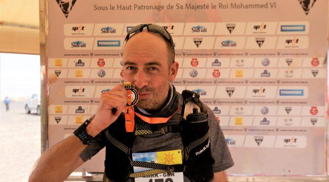 Mark Hillier holds his medal aloft after completing the Marathon des Sables