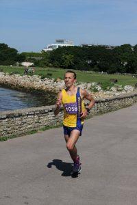 Jacek Cieluszecki by wall in Poole Half Marathon