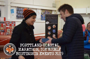 Ollie Stoten picks up his prize for 2nd place in the Portland Coastal Marathon