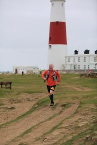 Andy Gillespie going past the lighthouse on day of the Jurassic Coast Challenge