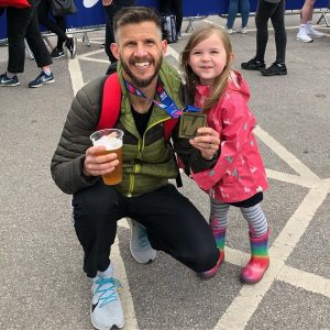Ant Clark with beer and medal after Manchester Marathon