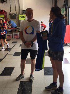 Andy Gillespie is presented with 100 Marathon Club medal