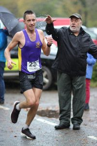 Stu Nicholas takes on some water at the Cornish Marathon