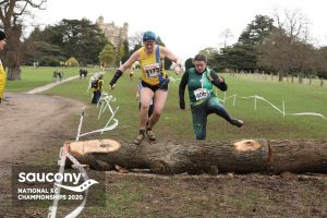 Annette Lewis jumps over a log in the National Cross Country Championships
