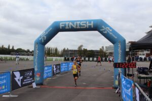 Isabel Cherrett crossing the finish line in the Newbury Racecourse 5k