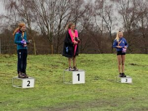 Neve East and Emily Coltman on the podiums at Trail X Winter Woodland Run
