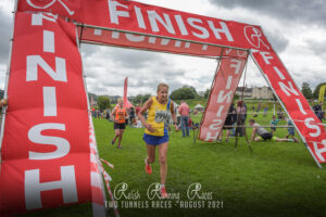 Heather Khoshnevis crosses the line in the Two Tunnels Marathon